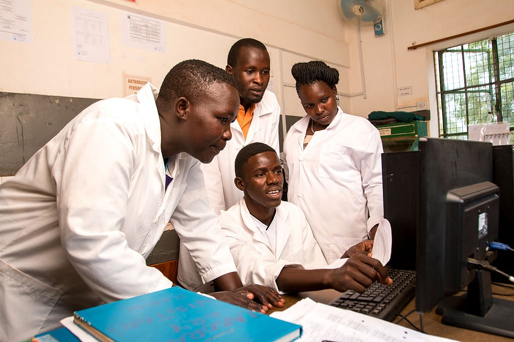 Clinical team wearing white gowns in Africa looking at a computer