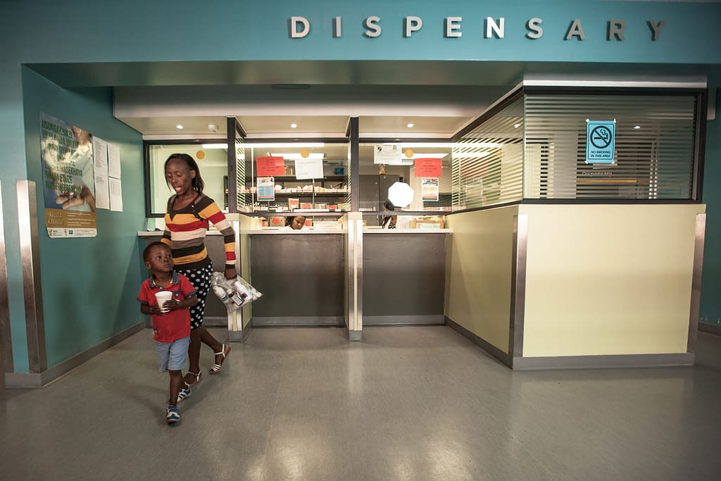 Mother and son collecting HIV medicines at hospital dispensary in Durban