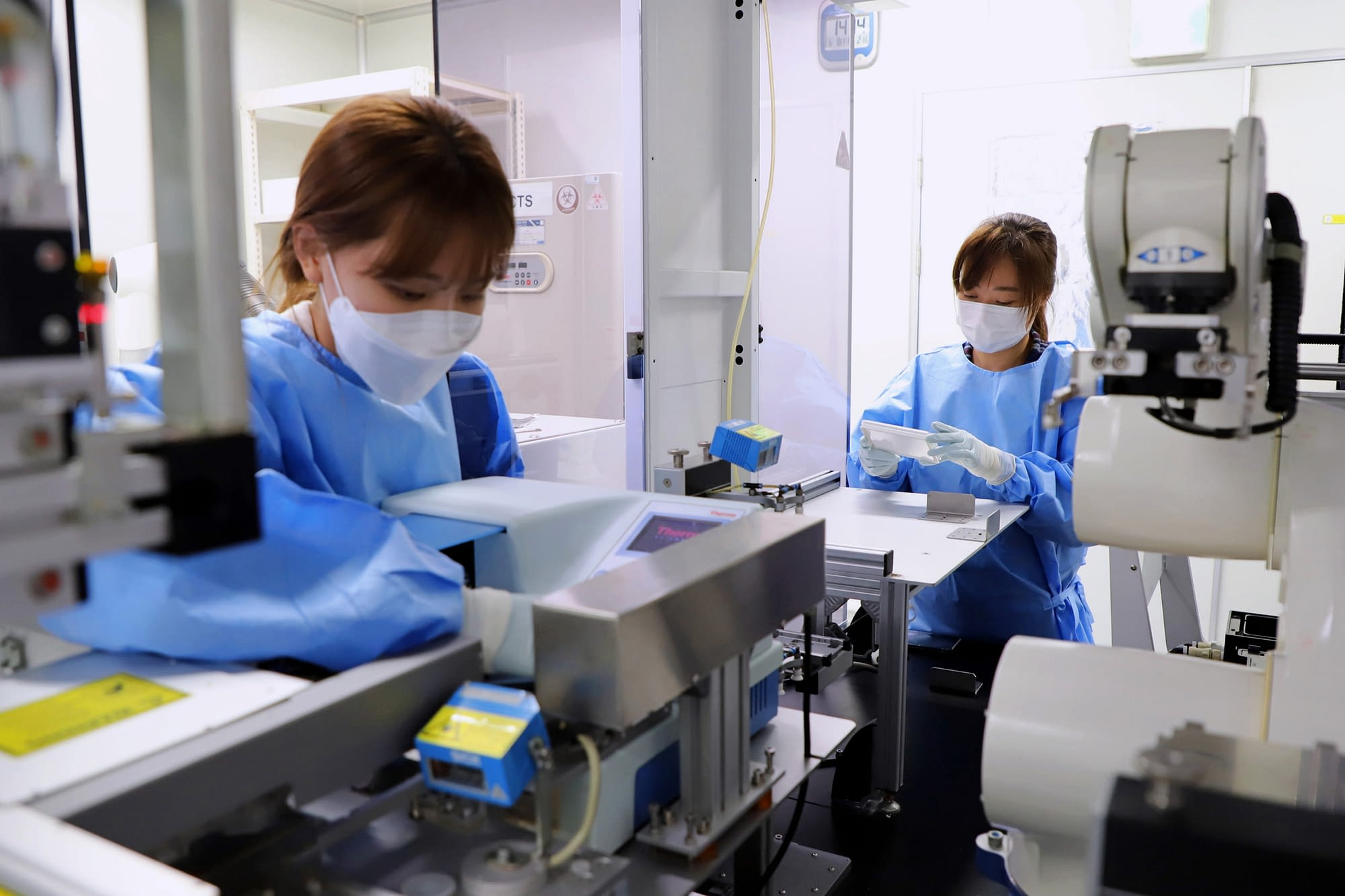 Researchers in operation of the cell-based screening platform in the biosafety level-2(BSL-2) laboratory