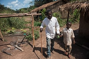 Father walking in rural village with a cane and holding his son's hand