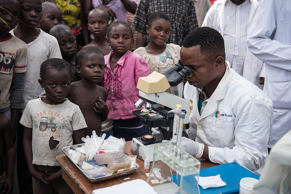 Medical staff looking into a microscope while screening patients in DRC