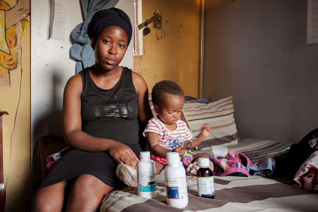 Mother sat on the bed with her son and his medication to treat HIV