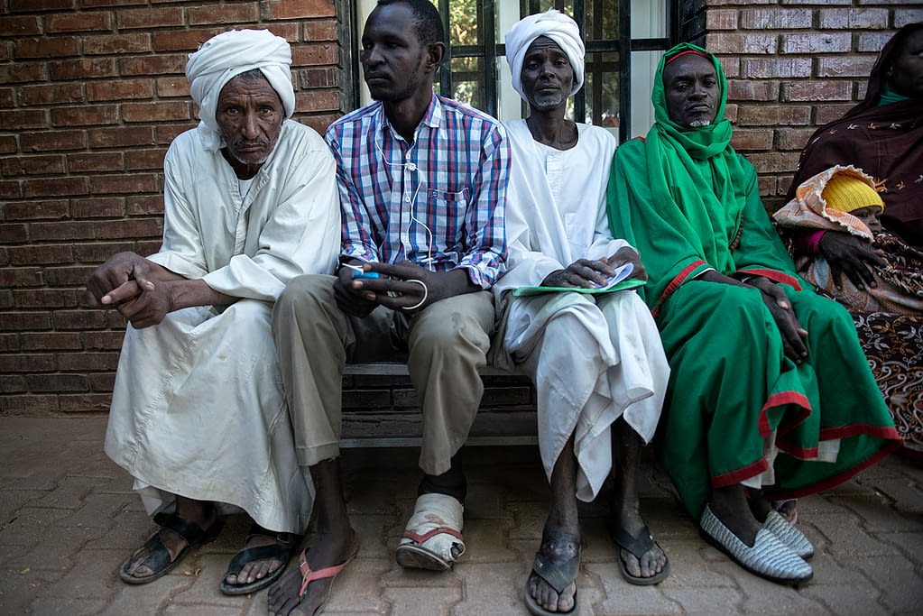 Mycetoma patients sitting in front of a hospital