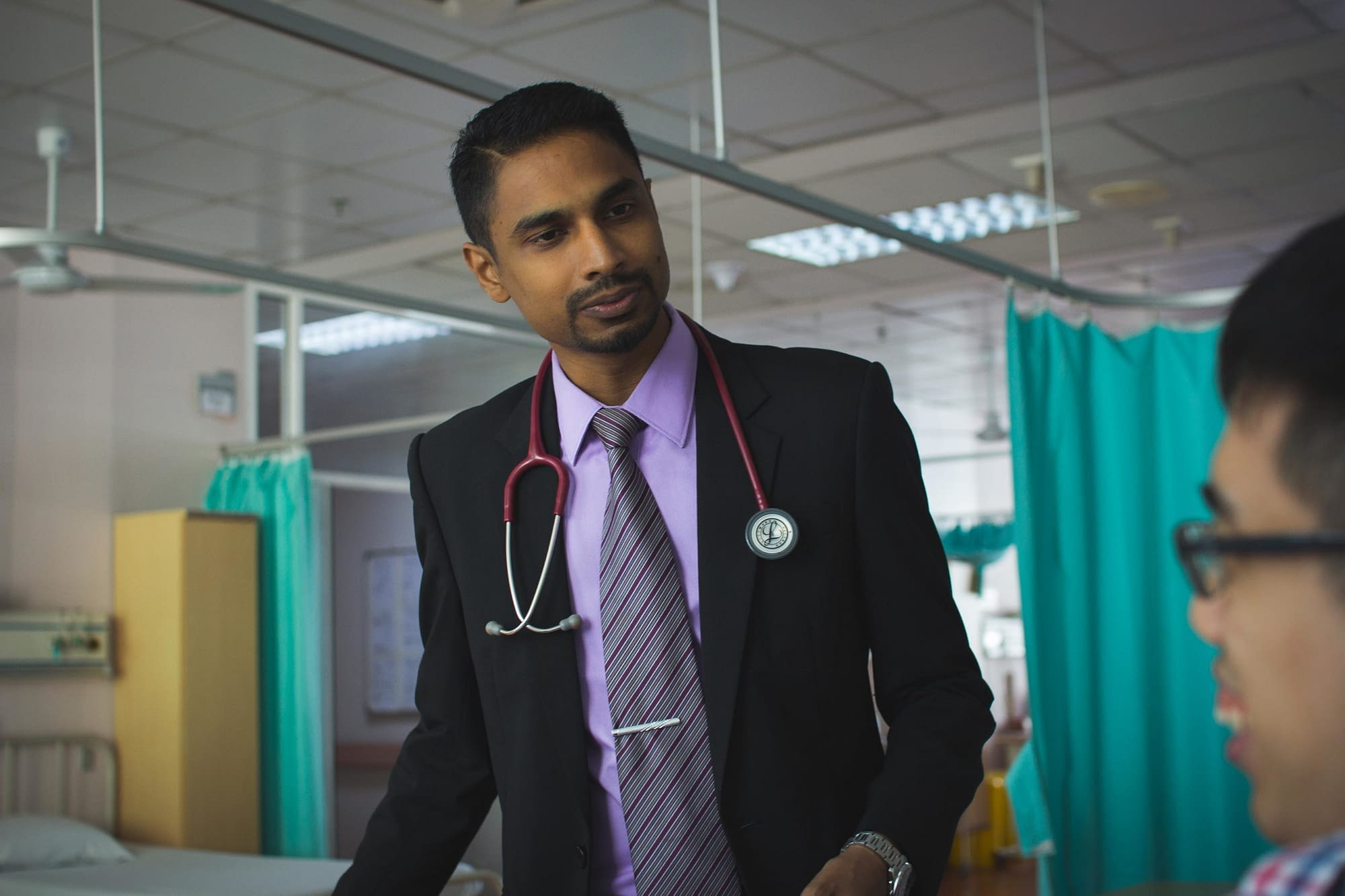 Malaysian doctor talking with a man in a hospital