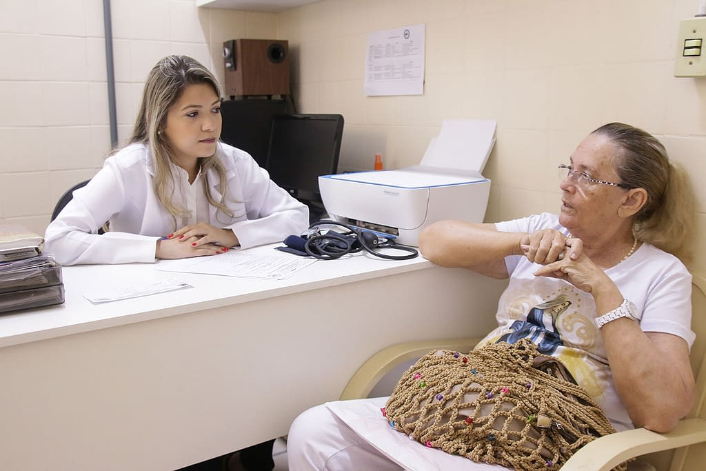 Woman sitting at a desk with a healthworker discussing