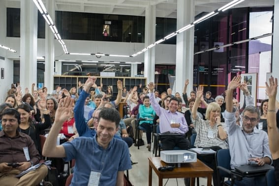 People raising their hands to vote