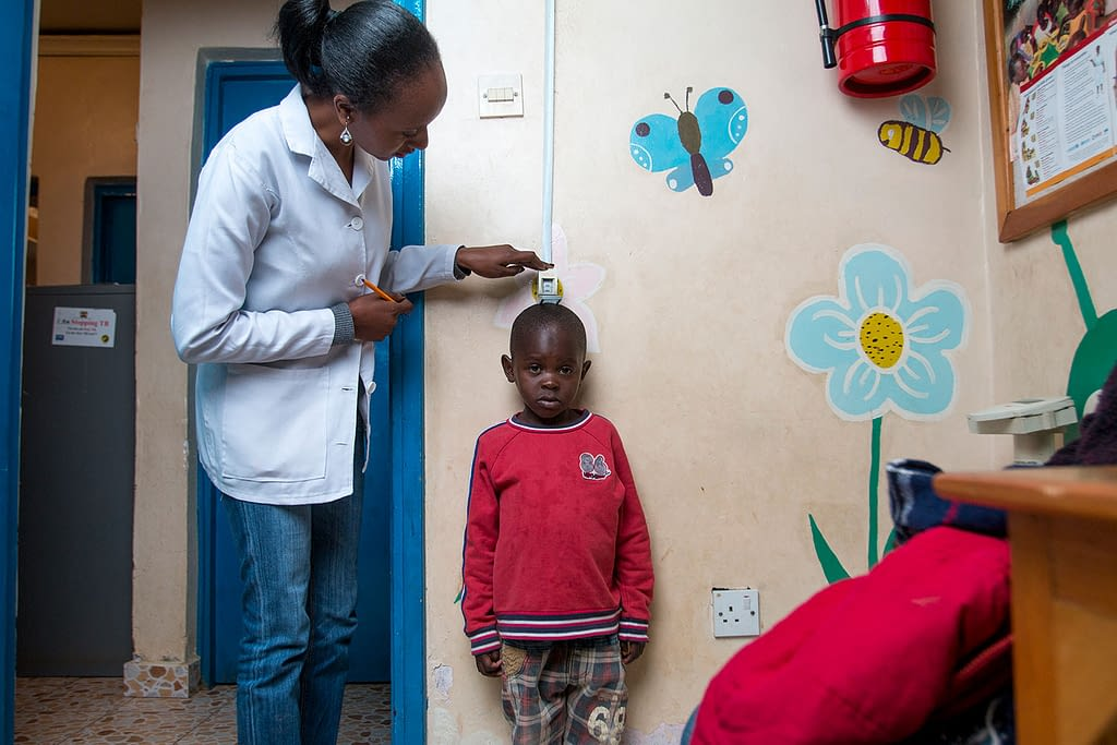 Little boy with paediatric HIV being measured by a nurse in a hospital