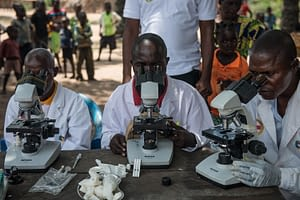 Healthworkers from mobile screening teams look through microscopes to check blood samples for sleeping sickness