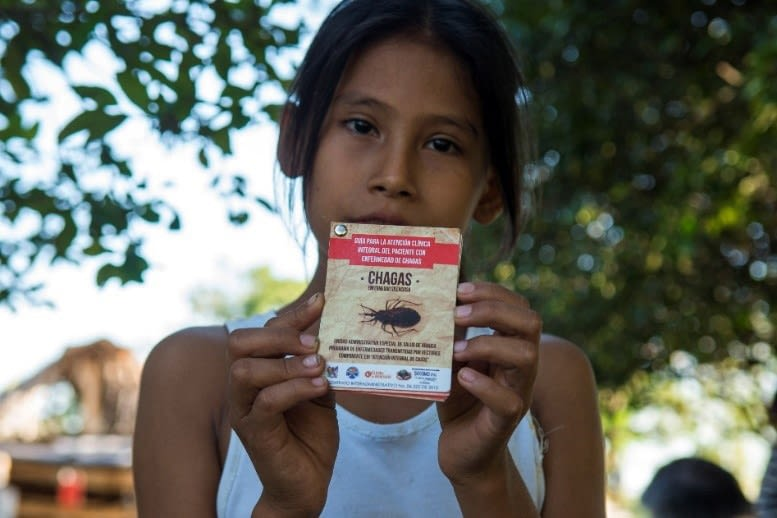 Young girl holding a flyer on Chagas disease