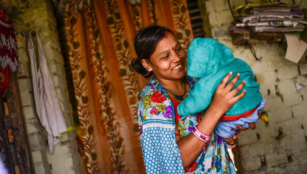 Woman holding her baby smiling