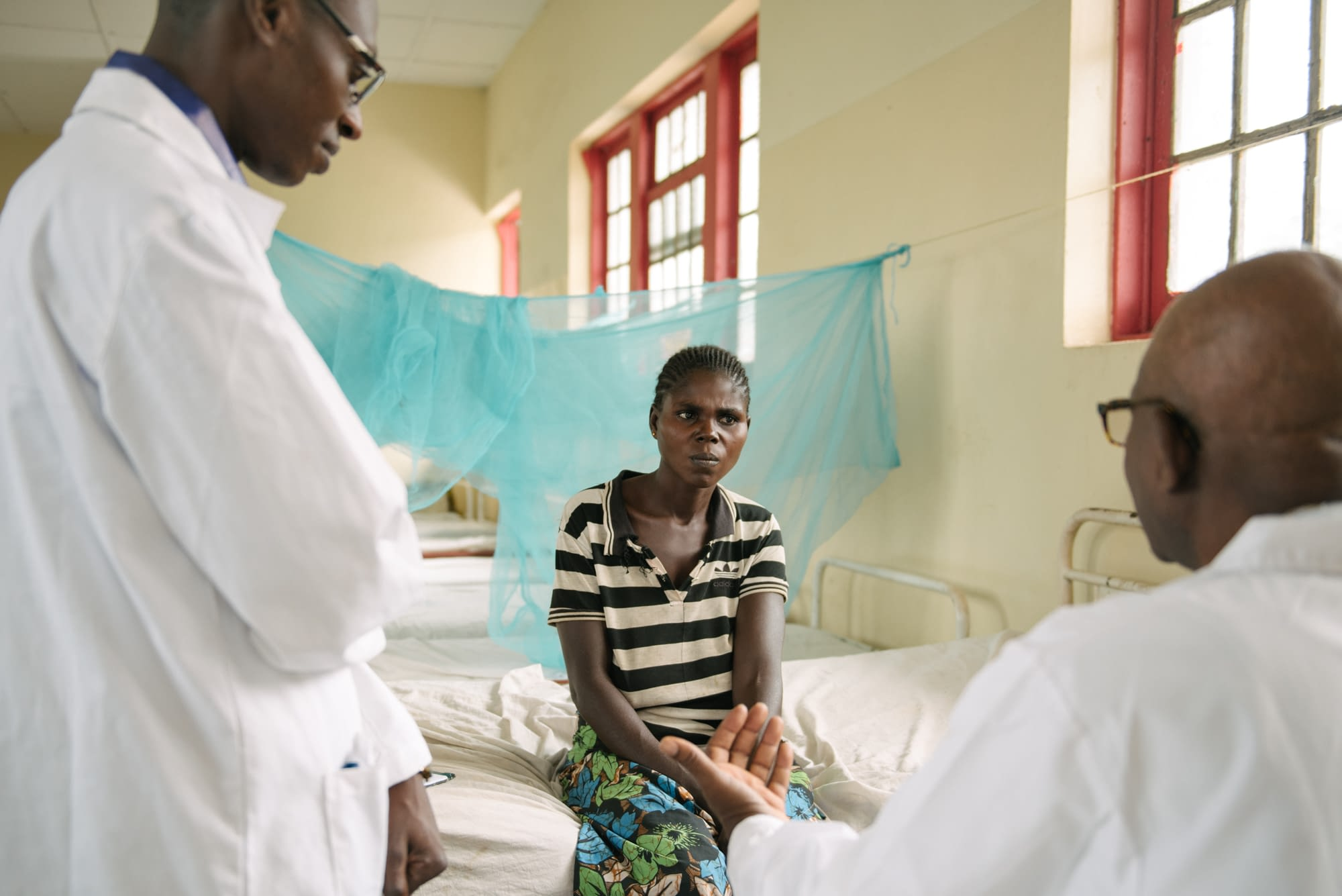 Doctors talking with patient in hospital
