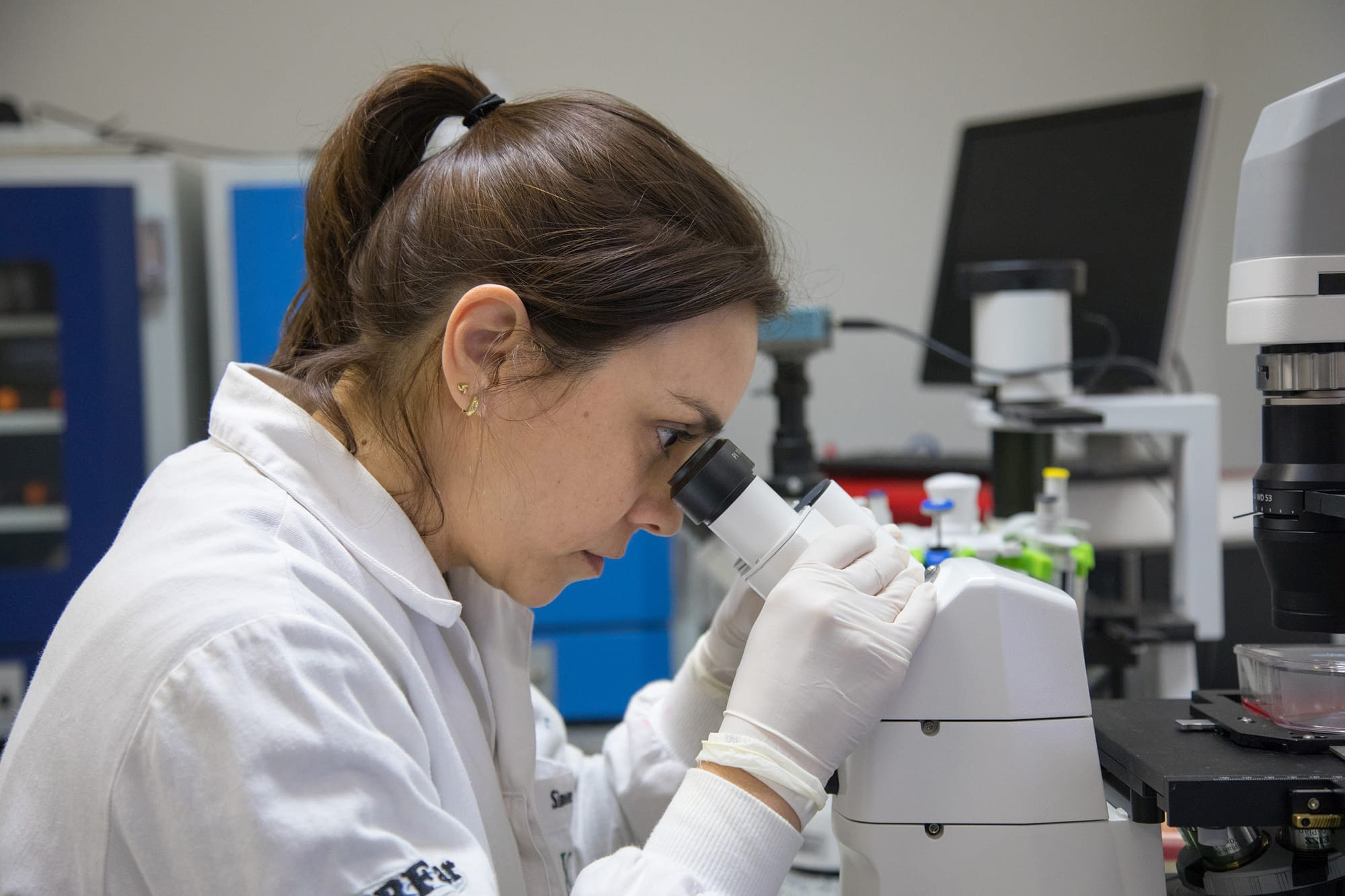 Female researcher looking in a microscope