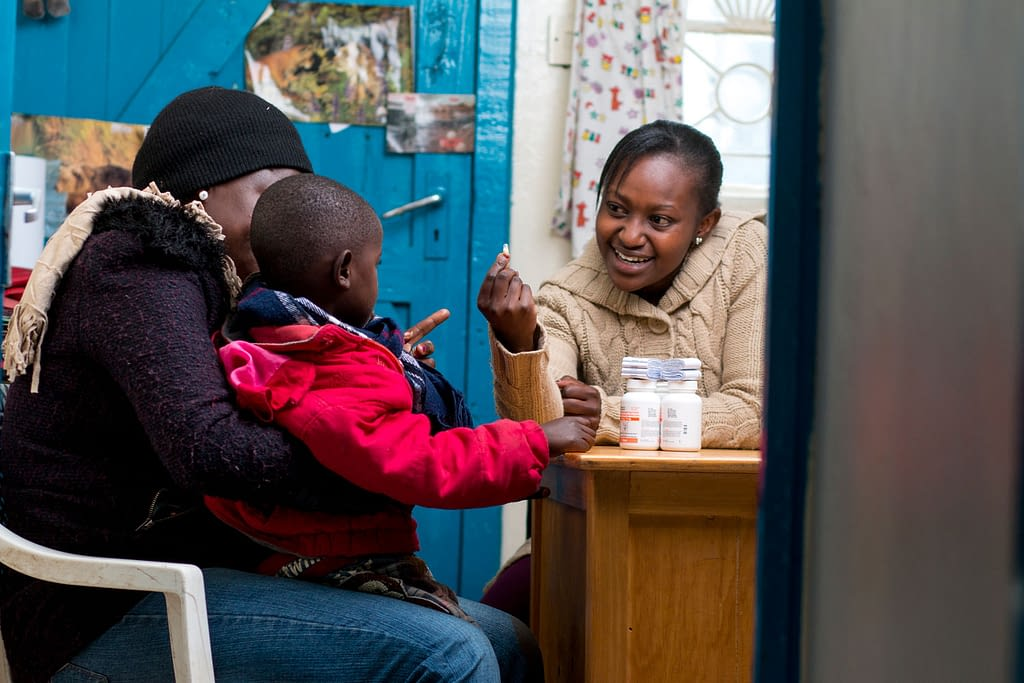 Nutritionist explains how to use the 2-in-1 pellets to a mother and her HIV-positive child in Kenya