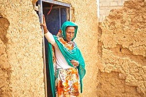 Woman standing in front of her door house in a rural village in Sudan
