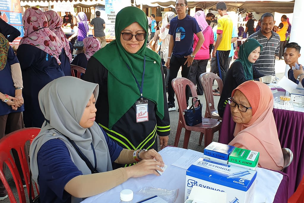 One of the clinical volunteers from Hospital Tengku Ampuan Afzan (HTAA) preparing to screen a woman for hepatitis C