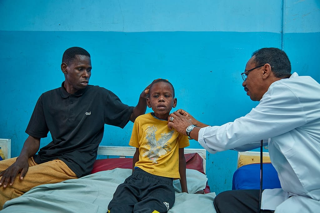 Little boy affected by PKDL in Sudan being examined by a Doctor, his father sitting next to him